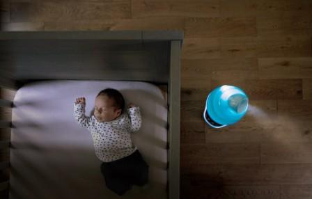 what does a humidifier do for babies - baby in a crib and a humidifier blowing mist